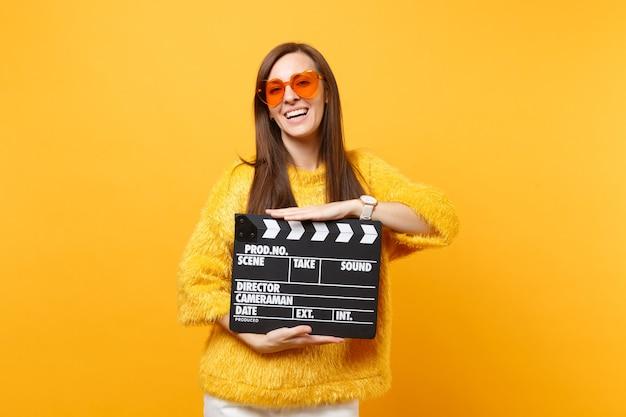 黄色の背景で隔離のカチンコを作る古典的な黒のフィルムを保持している毛皮のセーターオレンジハート眼鏡でうれしそうな若い女性の肖像画。人々は誠実な感情のライフスタイル。広告エリア。