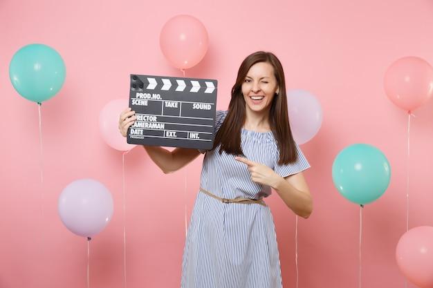 화려한 공기 풍선이 있는 분홍색 배경에 클래퍼보드를 만드는 고전적인 검은색 필름에 검지 손가락을 들고 깜박이는 파란색 드레스를 입은 즐거운 젊은 여성의 초상화. 생일 휴일 파티.