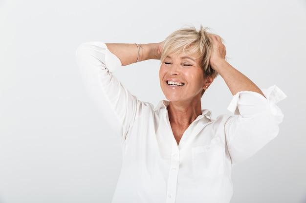 彼女の頭をつかんで、スタジオの白い壁に隔離されたカメラで笑っている短いブロンドの髪を持つ楽しい大人の女性の肖像画