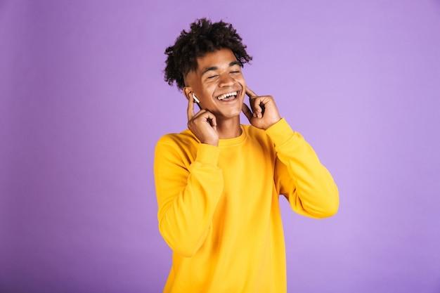 紫色の背景の上に分離されたbluetoothイヤホンで音楽を聴きながら、スタイリッシュなアフロヘアスタイルの笑顔で楽しいアフリカ系アメリカ人の男の肖像画