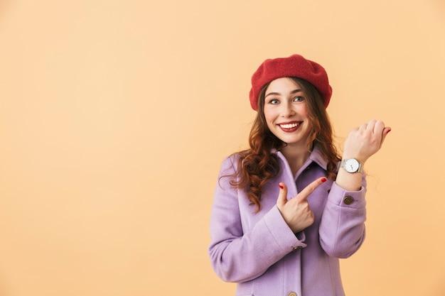 고립 된 서있는 동안 그녀의 손목 시계를 보여주는 코트와 모자에 즐거운 소녀 20 대의 초상화