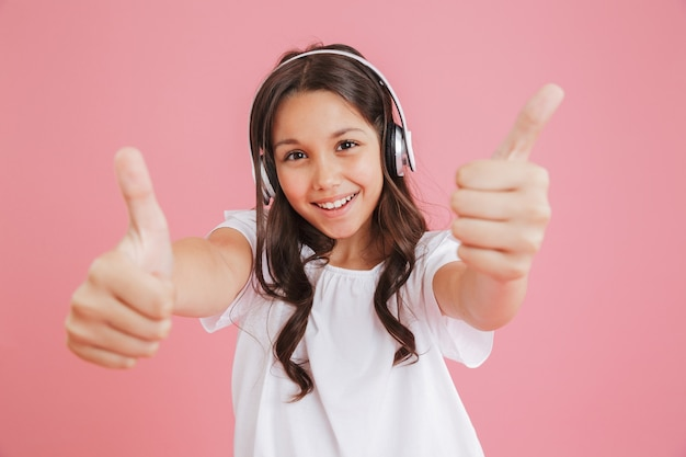 ピンクの背景で隔離のワイヤレスヘッドフォンを介して音楽を聴きながら両手でカメラに親指を示すカジュアルな服を着た楽しい女の子8-10の肖像画