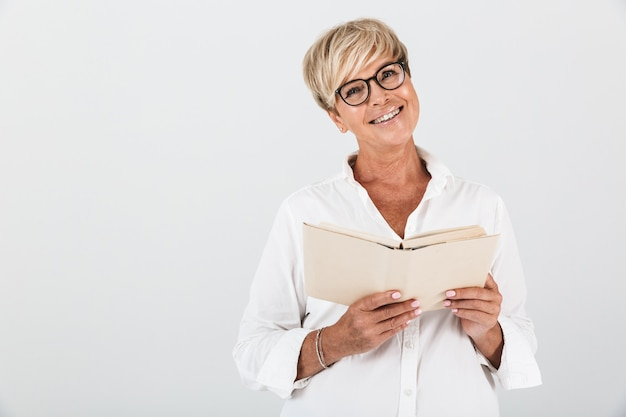 Портрет радостной женщины средних лет в очках, читающей книгу, изолированную над белой стеной в студии