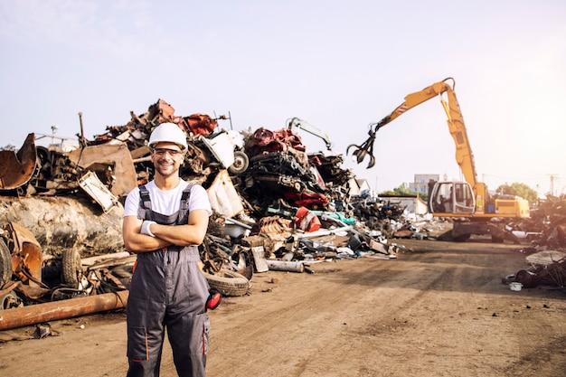 고철 재활용 센터에 서 있는 폐차장 작업자의 초상화.