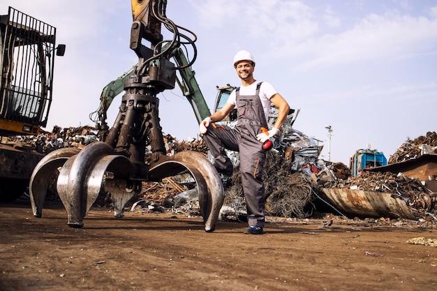 고철 부품을 들어 올리는 데 사용되는 산업 기계 서 있는 폐차장 노동자의 초상화