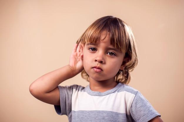 Портрет мальчика малыша, подслушивающего разговор. концепция детей и эмоций