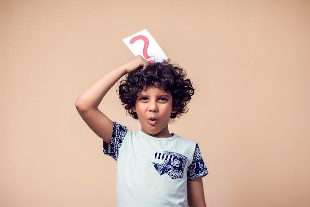 疑問符の付いたカードを保持している子供男の子の肖像画。子供の頃と教育のコンセプト