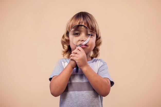 돋보기를 들고 아이 소년의 초상화입니다. 어린 시절과 발견 개념