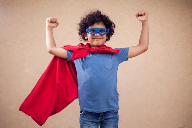 슈퍼 히어로의 의상에서 곱슬 머리를 가진 꼬마 소년의 초상화. 어린 시절과 성공 개념
