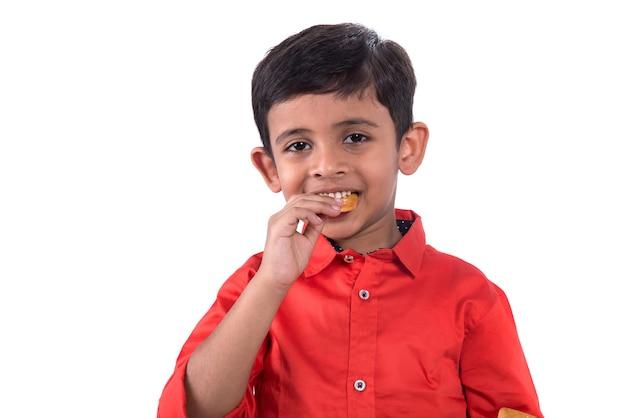 Портрет ребенка, едящего печенье на белой стене