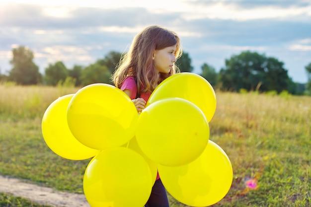 黄色の風船、自然空の牧草地の背景を持つ子供の女の子の肖像画。子供の頃、休日、誕生日、子供の概念