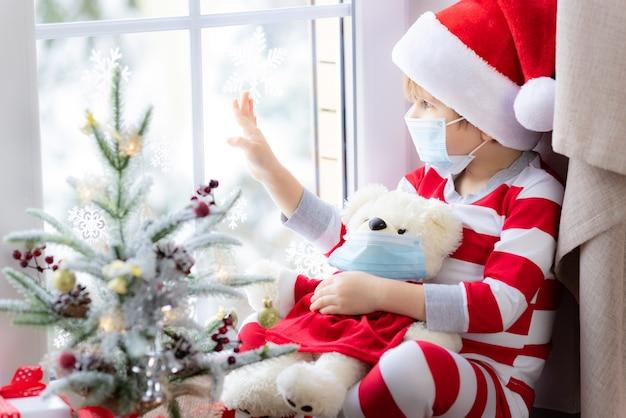 코로나바이러스 covid19 전염병 개념 동안 의료 마스크 크리스마스 휴가를 쓴 아이의 초상화