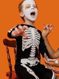 不気味なハロウィーンの衣装を持つ子供の肖像画