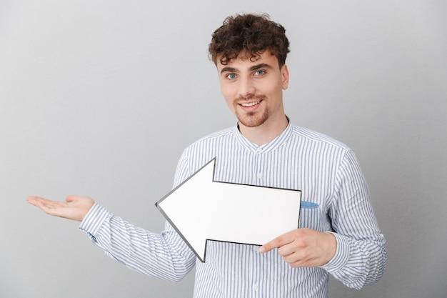 灰色の壁の上に分離された空白のコピースペース矢印ポインターを保持しているシャツに身を包んだ親切な美しい男の肖像画