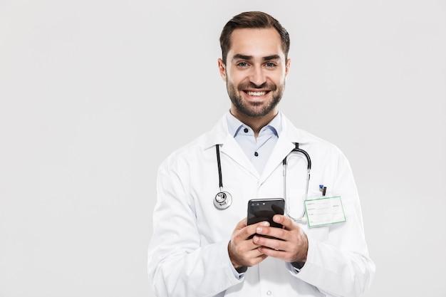 Портрет доброго молодого врача со стетоскопом, работающего в клинике и держащего мобильный телефон, изолированного над белой стеной