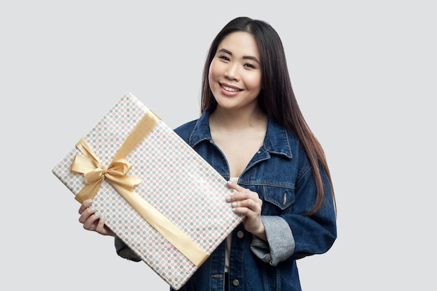 Портрет милой привлекательной молодой азиатской девушки в синей джинсовой куртке, стоящей и держащей настоящий момент с желтым бантом и зубастой улыбкой, смотрящей в камеру. крытый, изолированный, студийный снимок, серый фон