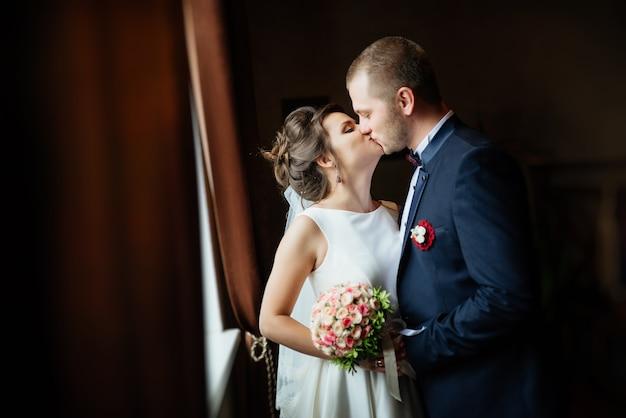 窓の近くに暗い固体のインテリアで花嫁と新郎にキスの肖像