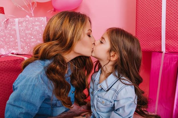 背景にカラフルなギフトボックスとトレンディなビンテージジャケットで巻き毛の母と娘にキスの肖像画。魅力的な誕生日の女の子とポーズの子供のパーティーで楽しんでエレガントな若い女性