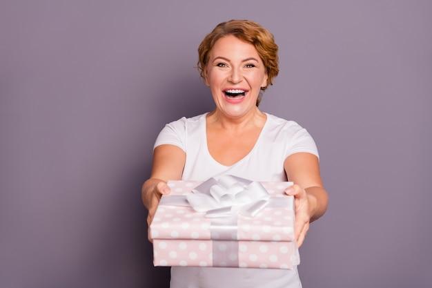 보라색에 고립 된 선물을 들고 흰색 티셔츠에 여자의 초상화