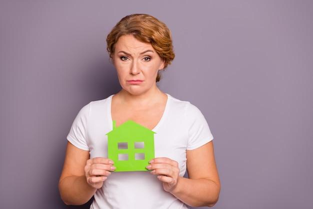 紫で隔離紙の家を保持している白いtシャツの女性の肖像