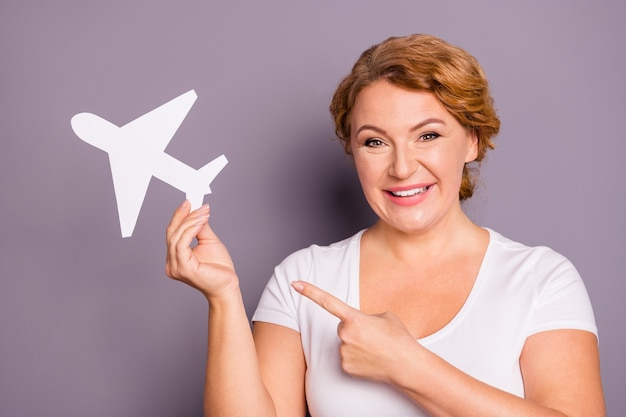 Портрет дамы в белой футболке, держащей бумажный самолетик, изолированный на фиолетовом