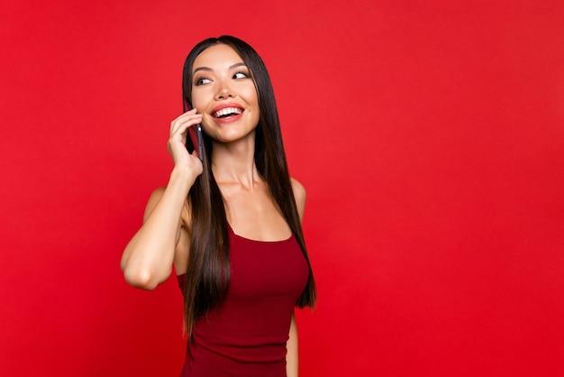 女性の肖像画は、赤い壁に孤立した笑いを振り返る電話で話す