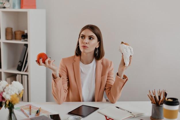 사무실에서 짧은 머리를 가진 여자의 초상화입니다. 생각에 비즈니스 우먼 햄버거 또는 건강 한 사과를 먹는 것을 선택합니다.