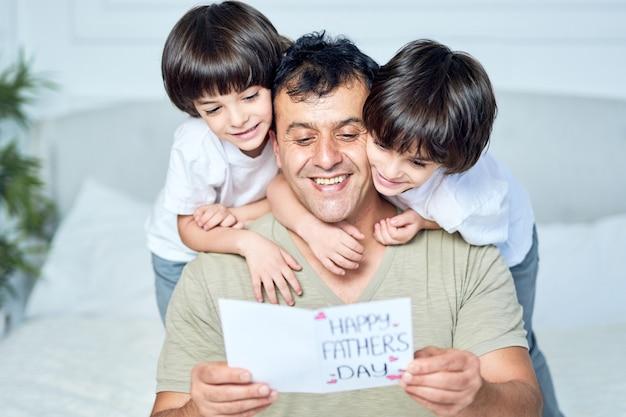 ラテン系の父親が幸せそうに見え、2人の男の子が父親を抱きしめ、手作りのはがきを渡し、父の日に挨拶し、家で一緒に時間を過ごしている様子の肖像画。父権、子供たち