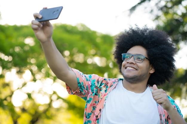 Портрет латинского мужчины, делающего селфи со своим мобильным телефоном, стоя на открытом воздухе