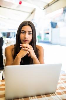 彼女のラップトップを屋外で使用するガラスのラテン女性の肖像画。巻き毛を持つ魅力的なフリーランサーの女性がストリートバーに座って、ネットブックで彼女のリモート作業をしています