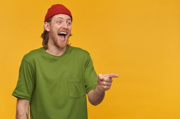 Портрет смеющегося, взрослого человека со светлой прической и бородой. в зеленой футболке и красной шапке. смотрит и указывает пальцем вправо на пространство для копирования, изолированное над желтой стеной
