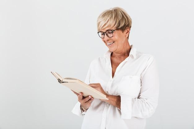 Портрет смеющейся взрослой женщины в очках, читающей книгу, изолированную над белой стеной в студии