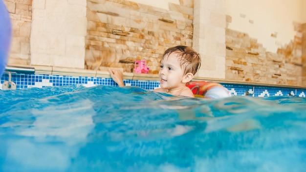 Портрет смеющегося и улыбающегося 3-летнего маленького мальчика, плавающего с надувным красочным кольцом и играющего с пляжным мячом в бассейне