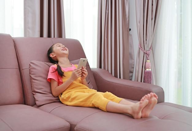 自宅のリビングルームのソファでスマートフォンを再生しながら笑っているアジアの小さな女の子の子供の肖像画