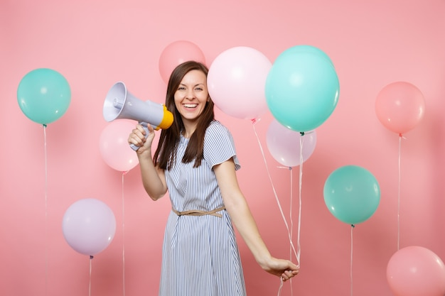 Портрет смеющейся привлекательной молодой женщины, носящей голубое платье, мигает, держа красочные воздушные шары и мегафон на пастельно-розовом фоне. праздник дня рождения, концепция искренних эмоций людей.