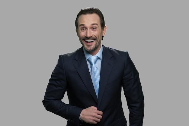 灰色の背景に笑うビジネスマンの肖像画。大喜びのビジネスマンは、陽気な何かを激しく笑っています。