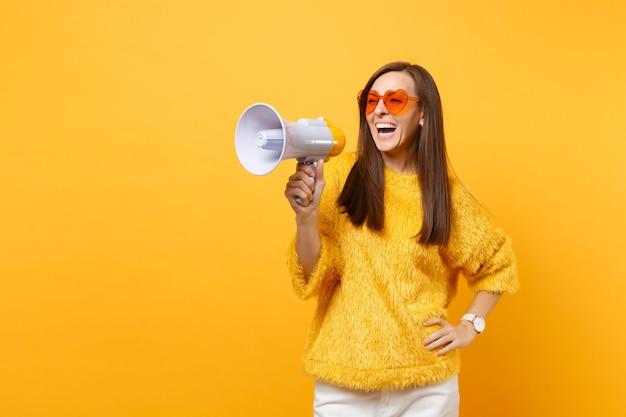 明るい黄色の背景に分離されたメガホンを保持している毛皮のセーター、オレンジ色のハートの眼鏡で笑っている陽気な若い女性の肖像画。人々の誠実な感情、ライフスタイルのコンセプト。広告エリア。
