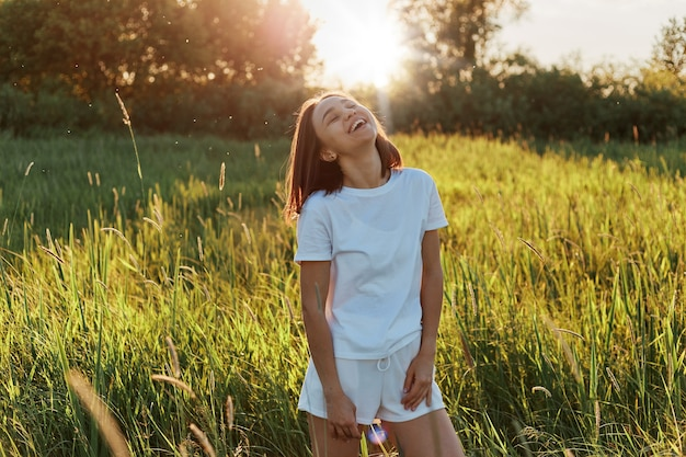 캐주얼 스타일 폐쇄, 여름을 즐기고, 그린 필드에서 시간을 보내고, 신선한 공기를 호흡하는 이빨 미소로 여성을 입고 웃는 어두운 머리 소녀의 초상화.
