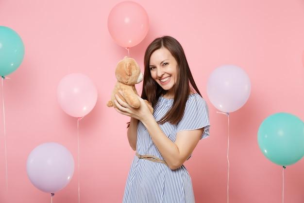 Портрет смеющейся счастливой молодой женщины в синем платье, держащей плюшевую игрушку плюшевого мишку на пастельно-розовом фоне с красочными воздушными шарами. праздник дня рождения, концепция искренних эмоций людей.