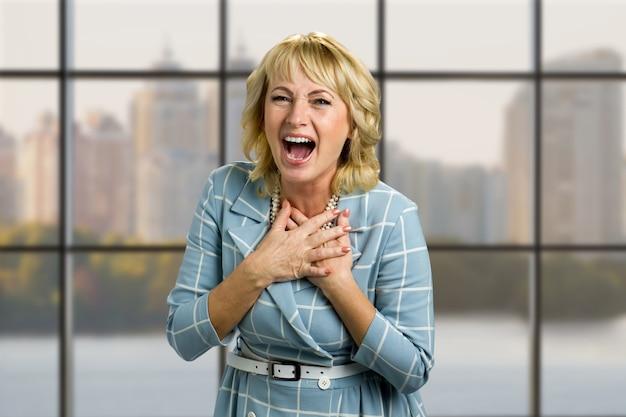 笑う成熟した女性の肖像画。胸に手をつないで、オフィスの窓に大きく開いた口で笑っている大人の女性。