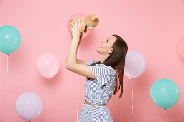 Портрет смеющейся довольно счастливой молодой женщины в голубом платье, держащей плюшевую игрушку плюшевого мишку на пастельно-розовом фоне с красочными воздушными шарами. праздник дня рождения, концепция искренних эмоций людей.