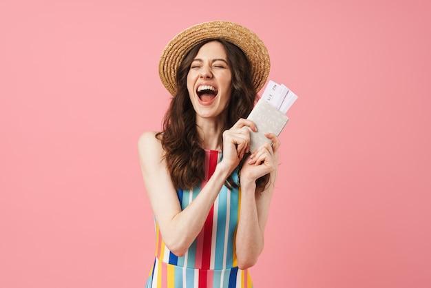 チケットとパスポートを保持しているピンクの壁の上に孤立してポーズをとって喜んで叫んで笑う若いかわいい女性の肖像画