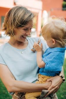 Портрет смеющейся женщины, держащей своего ребенка