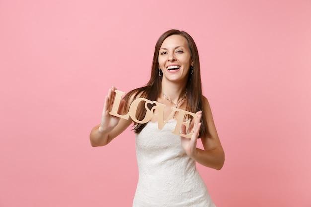 Портрет смеющейся женщины в элегантном белом платье, стоящей с деревянными буквами слова «любовь»