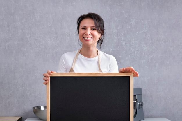 彼女の手にチョークボードを持つ笑う女性の肖像画。スペースをコピーして、モックアップします。
