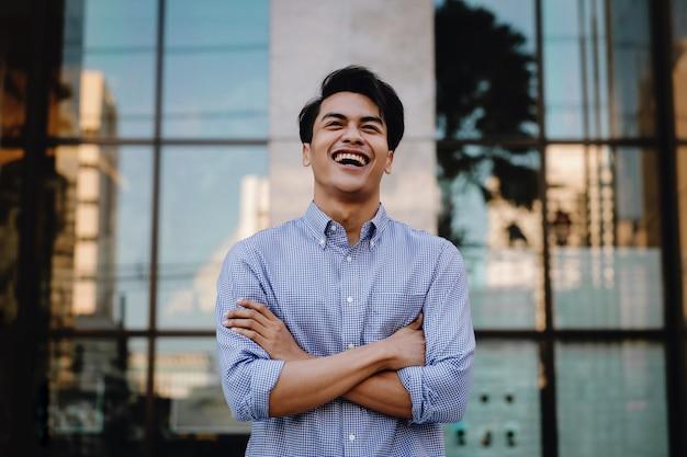 都市の若いアジア系のビジネスマンを笑いの肖像画。腕を組んでよそ見。