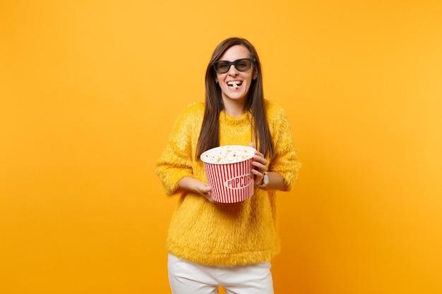 3d 아이맥스 안경을 쓰고 영화를 보고 웃고 있는 어린 소녀의 초상화는 밝은 노란색 배경에 격리된 양동이에서 팝콘을 먹습니다. 영화, 라이프 스타일 개념에서 사람들은 진실한 감정. 공간을 복사합니다.