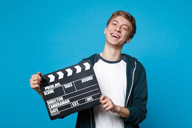 カジュアルな服を着て笑っている若い男の肖像画は、青い壁に隔離されたカチンコを作る古典的な黒い映画を保持しています。人々の誠実な感情、ライフスタイルのコンセプト。