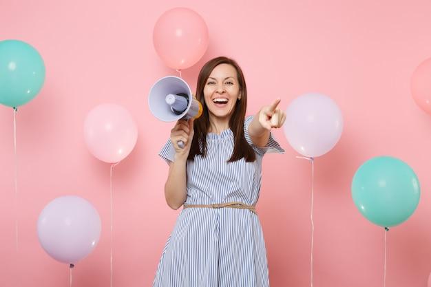 Портрет смеющейся молодой красивой женщины в голубом платье, держащей мегафон, указывая указательным пальцем на камеру на розовом фоне с красочными воздушными шарами. день рождения, праздник, у людей искренние эмоции.