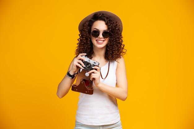 明るい黄色で隔離のレトロなビンテージ写真カメラで写真を撮る眼鏡で笑う若い女性の肖像画